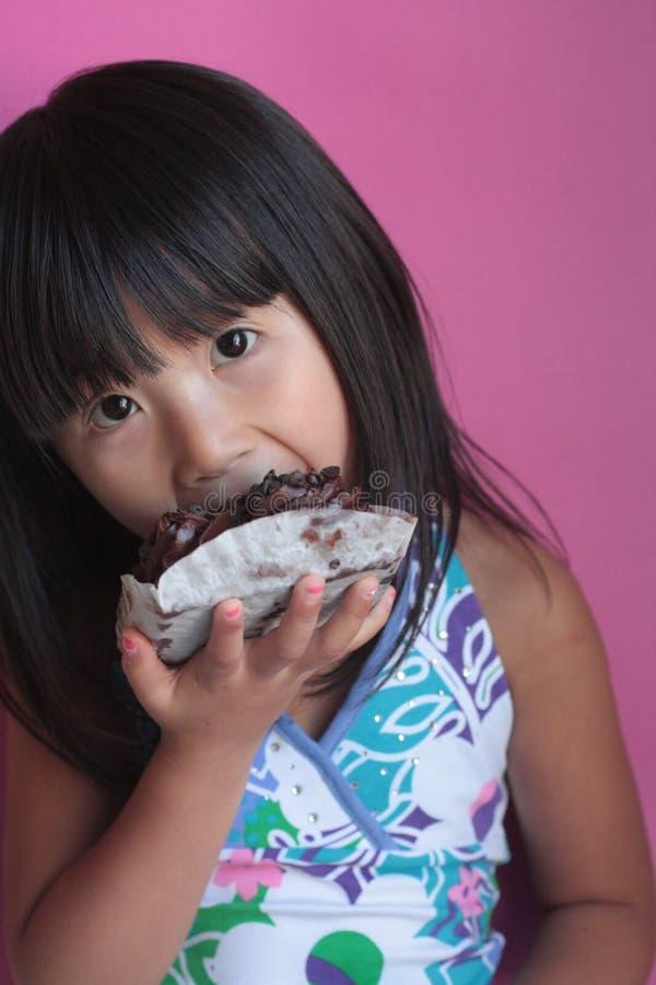 Chinse Weinig Aziatisch Meisje dat het dessert van de Brownie eet royalty-vrije stock afbeelding