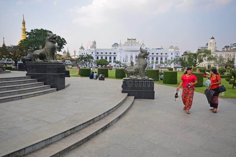 Chinthe-Statuen in Rangun Myanmar mit Schönheiten im Rot in der Front u. Tempel u. Kolonialbauten im Hintergrund lizenzfreie stockfotos