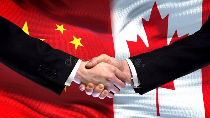 Chiny i Kanada uścisk dłoni, międzynarodowi przyjaźni powiązania, chorągwiany tło obrazy royalty free