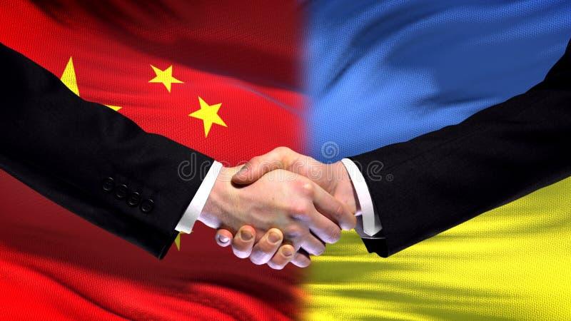 Chiny i Ukraina uścisk dłoni, międzynarodowi przyjaźni powiązania, chorągwiany tło zdjęcia royalty free