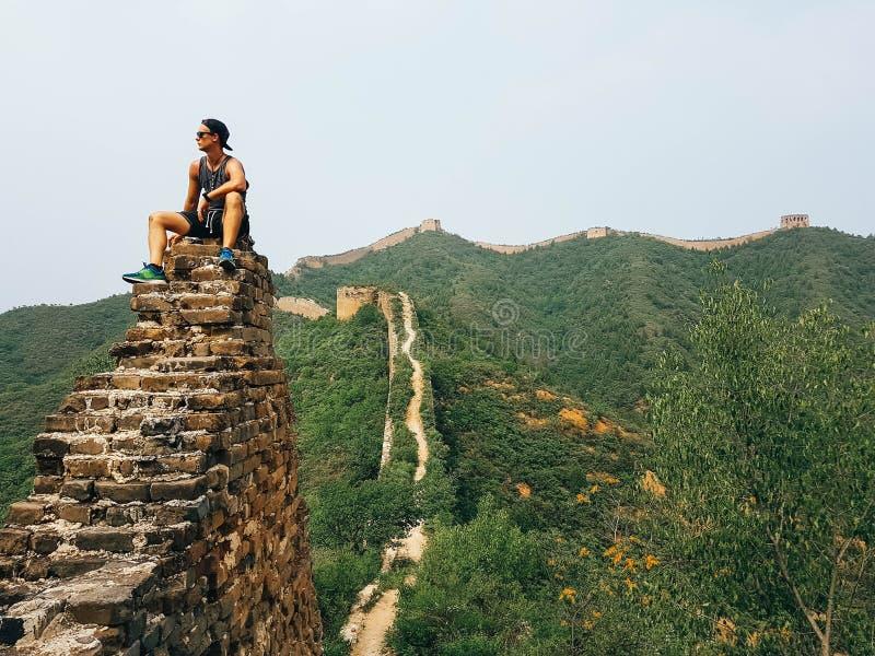 Chiny - mężczyzny obsiadanie na wielkim murze zdjęcia stock