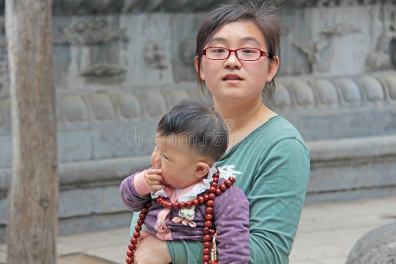 Chiny Shaolin, Kwiecień, - 11, 2012 Chińskich potomstw macierzysta dziewczyna z dzieckiem w jej rękach przy Shaolin monasterem, C obraz stock