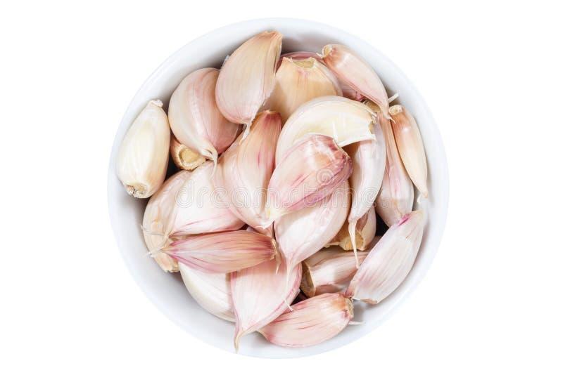 Chiodi di garofano di aglio da sopra la ciotola isolata su bianco fotografia stock