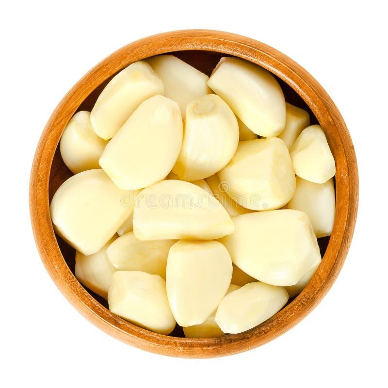 Chiodi di garofano di aglio sbucciati in ciotola di legno sopra bianco immagine stock