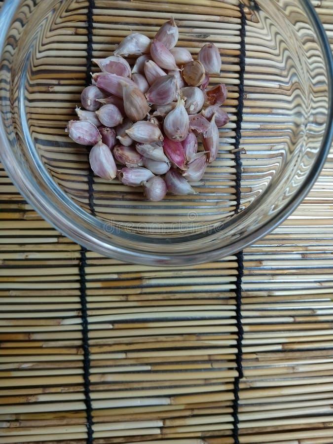 Chiodi di garofano di aglio in una ciotola di vetro sulla stuoia di legno immagine stock