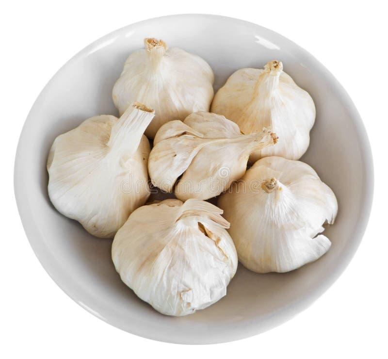 Chiodi di garofano di aglio sul piatto bianco. fotografia stock libera da diritti