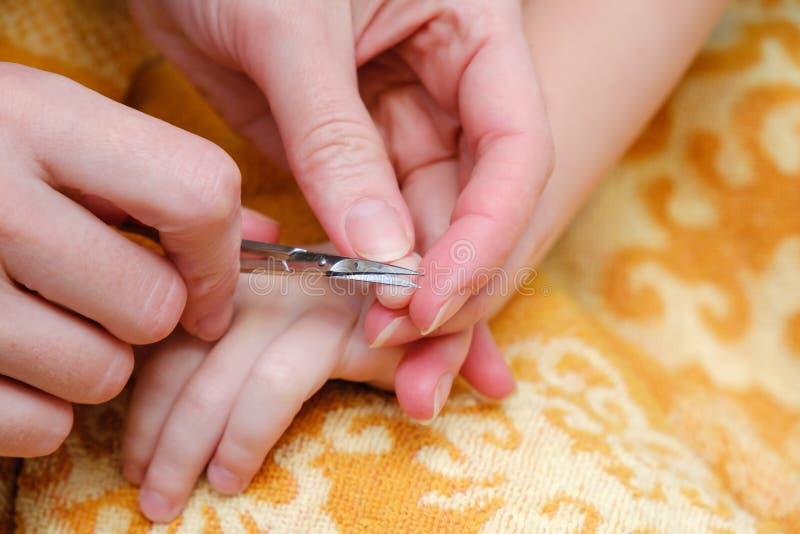 Chiodi di taglio della mano della madre di attività della famiglia per il bambino usando le forbici del chiodo immagini stock