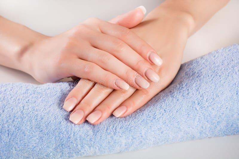 Chiodi francesi di Ombre sulle mani della donna del blu sull'asciugamano delicatamente fotografia stock libera da diritti
