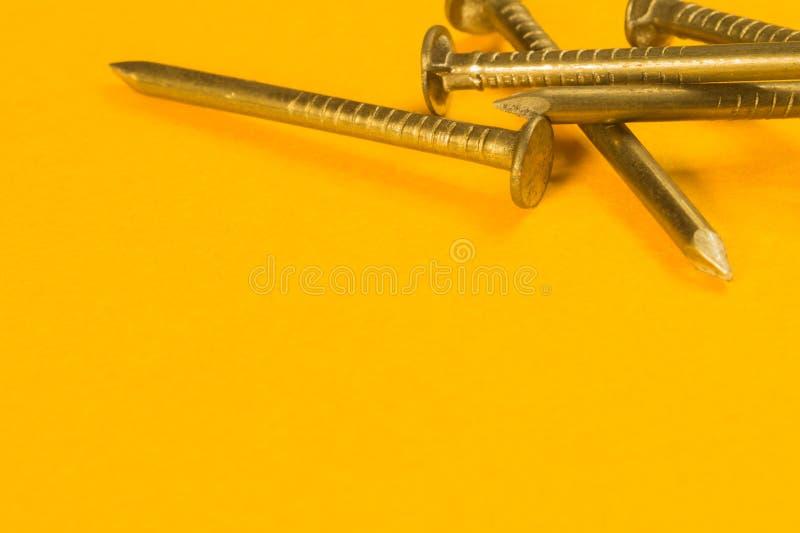 Chiodi su un fondo giallo fotografia stock libera da diritti