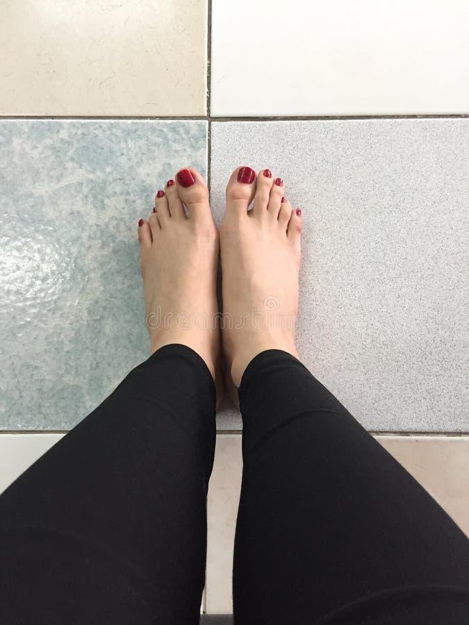 Chiodo rosso all'aperto dei piedi nudi di Selfie sul fondo del pavimento immagini stock libere da diritti