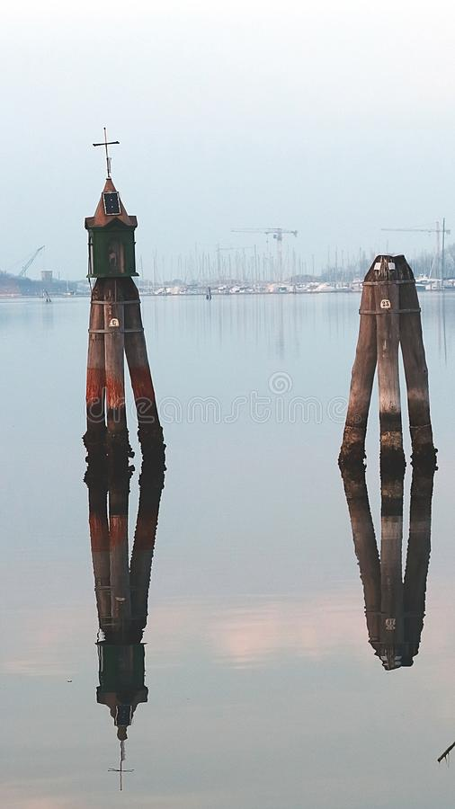 Chioggia, Italy. Venetian buoys in the harbour. Reflection stock image