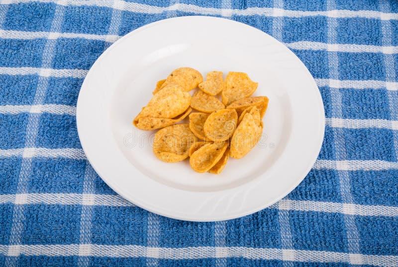 Chip di cereale sul piatto bianco e sull'asciugamano blu fotografia stock libera da diritti