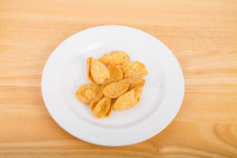 Chip di cereale sulla Tabella bianca di legno e del piatto immagini stock