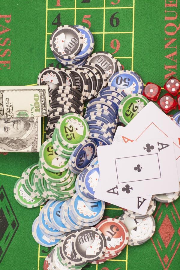Chip di poker, soldi, carte da gioco e dadi fotografie stock