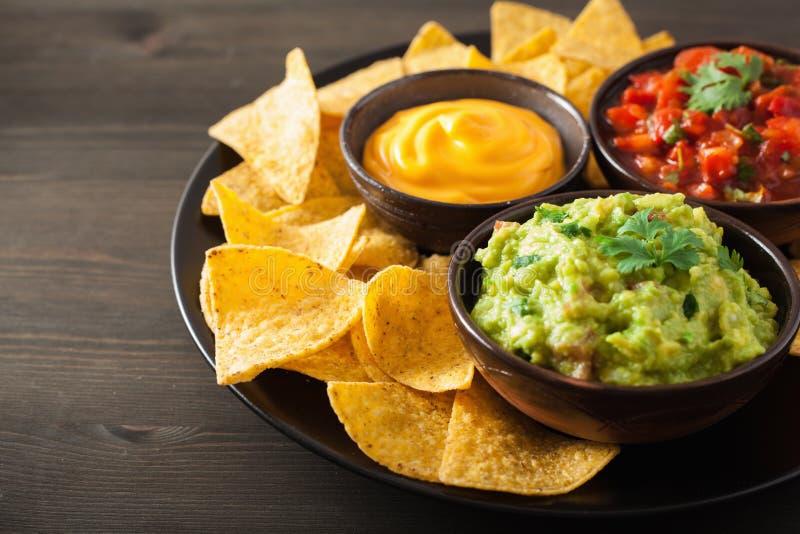 Chip di tortiglia messicani dei nacho con guacamole, salsa e formaggio d fotografia stock