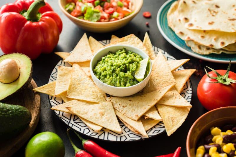 Chip di tortiglia messicani dei nacho del guacamole dell'alimento salsa e fagioli fotografia stock libera da diritti