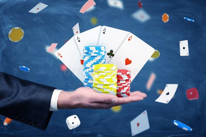 Chip e carte da gioco del casinò della tenuta della mano di un uomo d'affari con un fondo pieno delle carte e dei dadi fotografie stock libere da diritti
