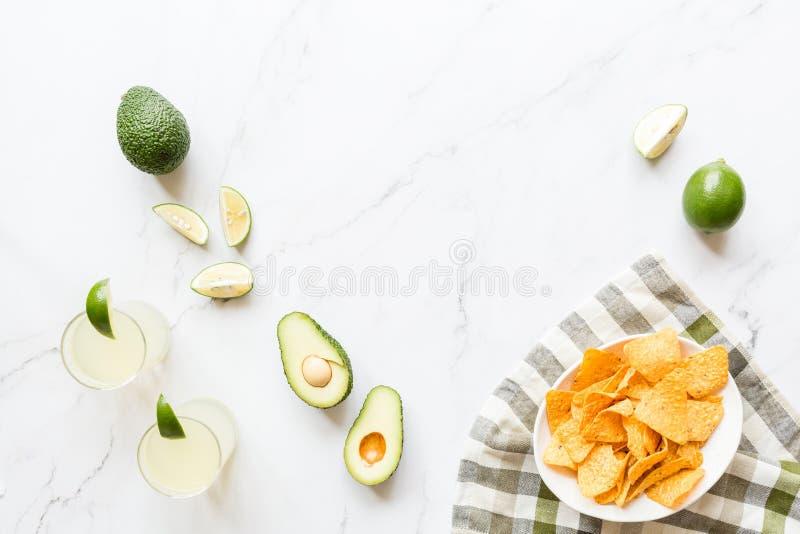 Chip freschi dell'avocado, della calce, della bevanda e del nacho che si trovano sul fondo di marmo Ricetta per il partito di Cin fotografia stock
