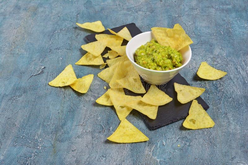 Chip messicani dei nacho con la salsa o la immersione verde del guacamole in ciotola bianca sul bordo nero dell'ardesia fotografia stock libera da diritti