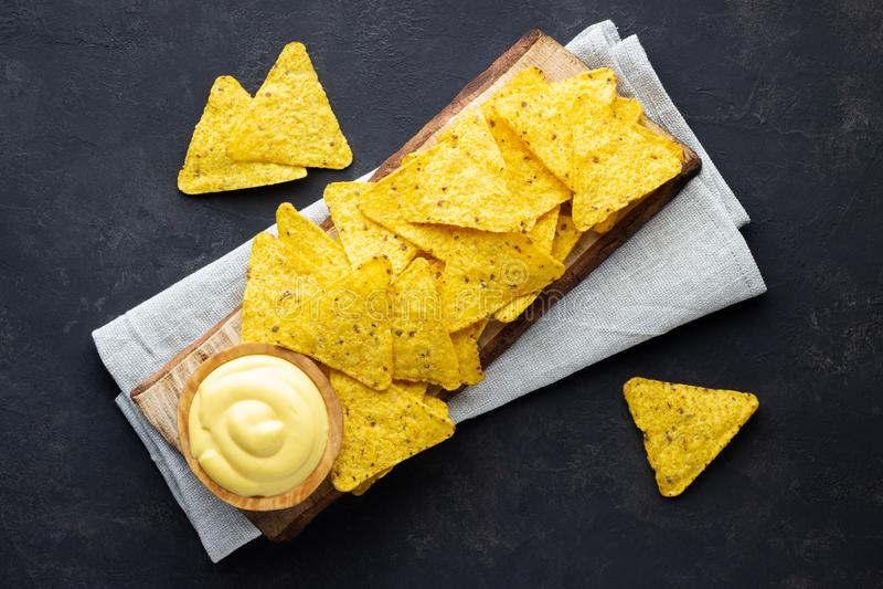 Chip messicani dei nacho sopra il bordo rustico di legno con la salsa di formaggio immagine stock libera da diritti