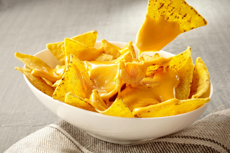 Chip pulled out of bowl of cheese covered nachos royalty free stock images