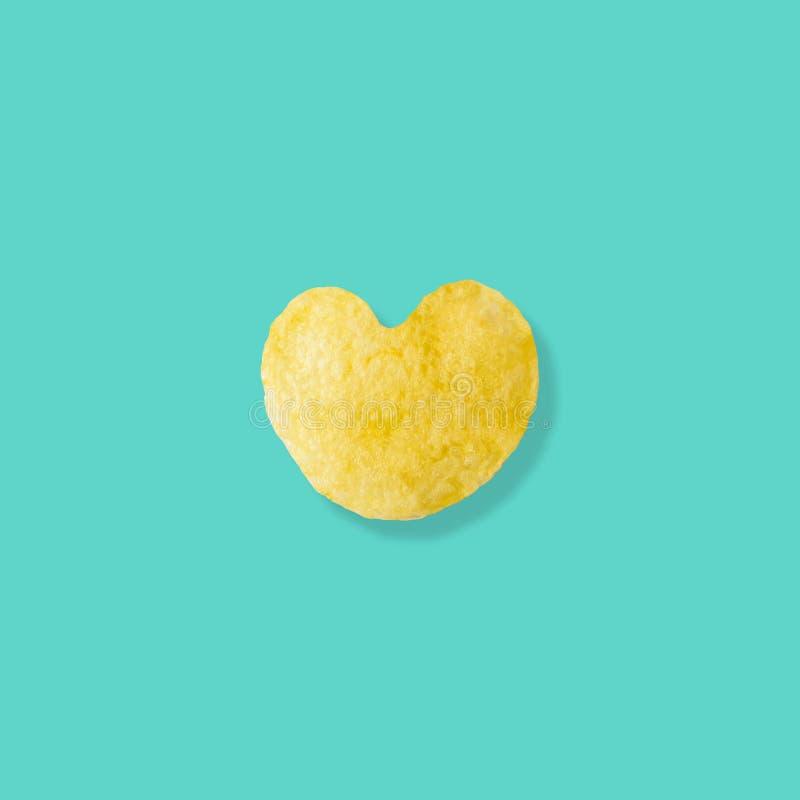 Chiper för hjärtaformpotatis på pastellfärgad blå bakgrund fotografering för bildbyråer