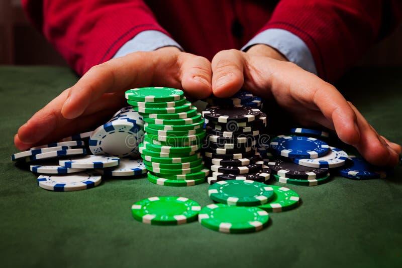 Chiper i förgrunden, i göra suddig av händerna av en man som rymmer chiper som spelar poker fotografering för bildbyråer