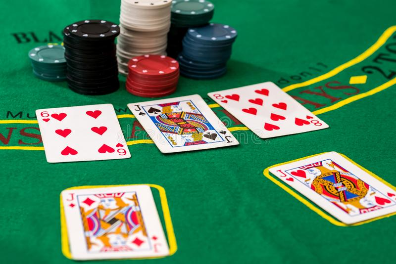 Chiper och pokerkort på en grön tabell royaltyfria foton