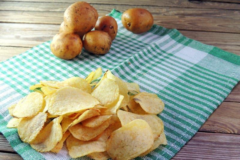 Chiper och rå potatisar arkivbild
