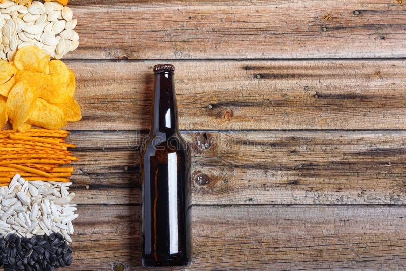 Chiper, smällare, frö, muttrar och flaska av nytt kallt öl på trätabellen arkivbilder