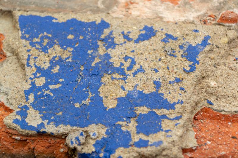Chipped concrete surface with blue paint coming off. Peeling blue paint stock images