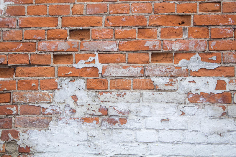 Chipped and peeling white paint on the old brick wall. stock photo
