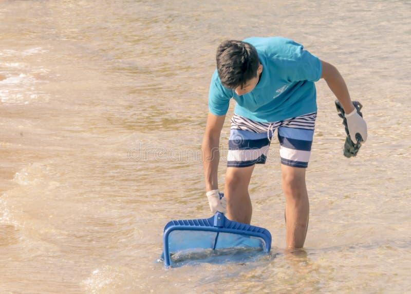 CHIPRE, KARAVAS, ALSANCAK - 10 DE JUNHO DE 2019: Menino novo que limpa a costa do lixo Homem que trabalha pelo mar usando ferrame imagem de stock