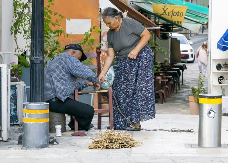 CHIPRE, NICOSIA - 10 DE JUNHO DE 2019: Pares gregos idosos de artesãos que fazem cadeiras de vime em uma rua da cidade Família tr foto de stock