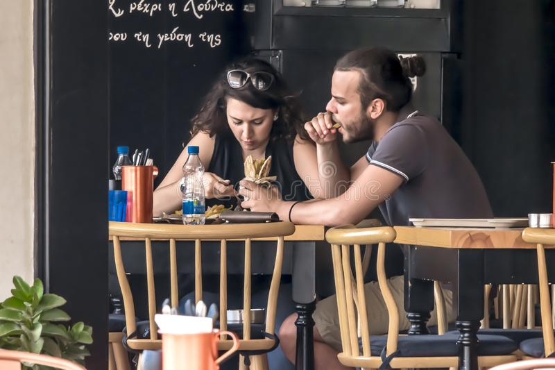 CHIPRE, NICOSIA - 10 DE JUNHO DE 2019: Pares novos que comem no restaurante exterior da rua Homem e mulher que apreciam o fast fo imagem de stock