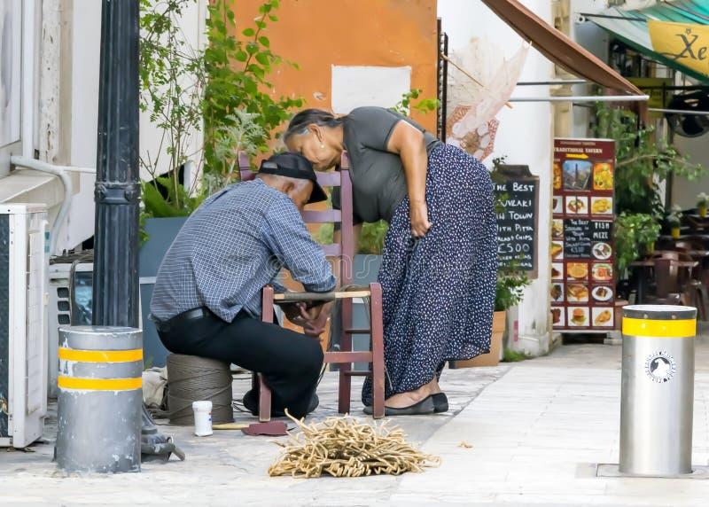 CHIPRE, NICOSIA - 10 DE JUNIO DE 2019: Pares griegos mayores pobres de los artesanos que hacen sillas de mimbre en una calle de l imagenes de archivo
