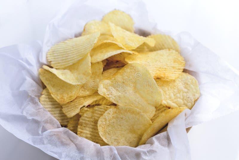 Chips in een kom van hout op een zwarte achtergrond wordt gemaakt die royalty-vrije stock fotografie