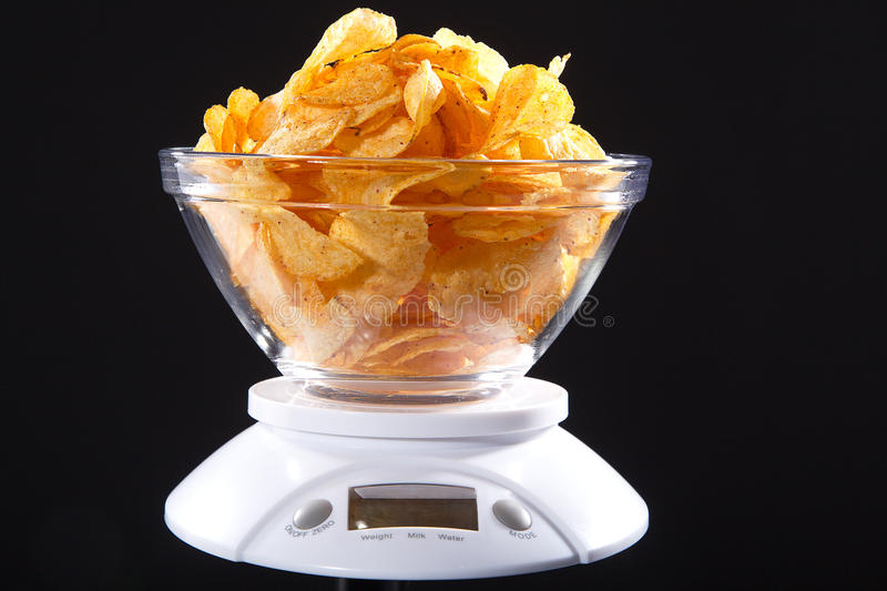 Chips. In glass bowl on kitchen scale stock image