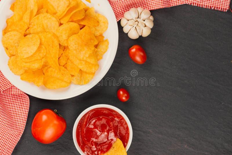 chips ketchuppotatisen ölmellanmål, sjukligt äta arkivbilder