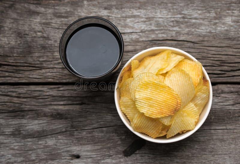 chips in kom met kola op houten lijstachtergrond, mening stock fotografie
