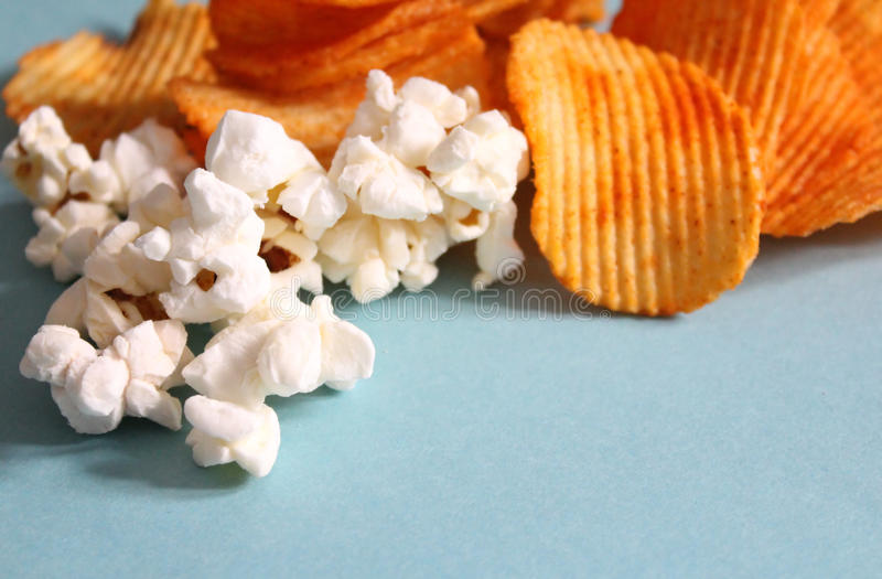Chips and popcorn. Lots of chips and popcorn with blue background stock photography