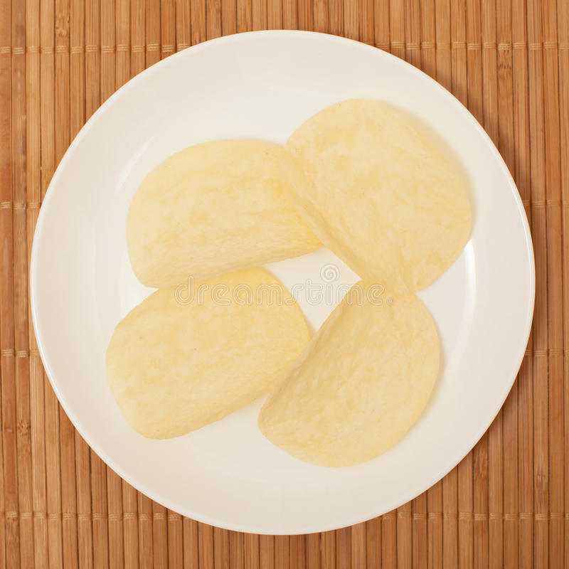 Chips. Potato chips on a plate on a bamboo stand royalty free stock images