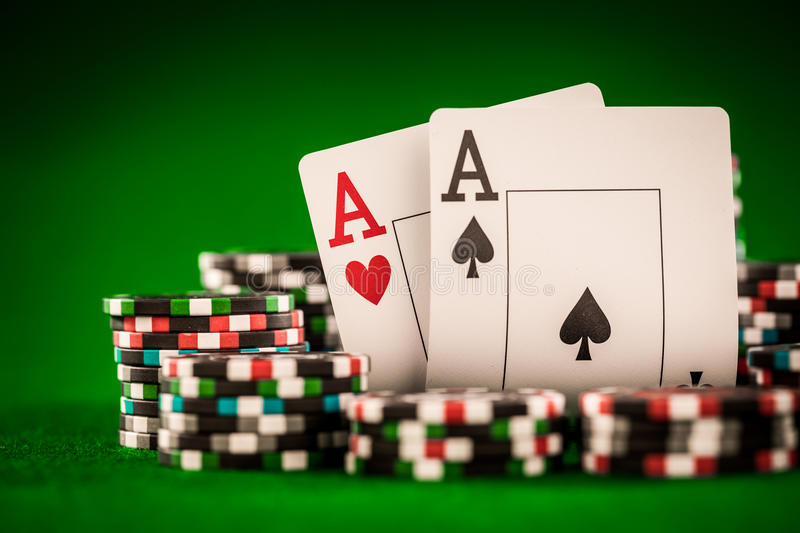Chips and two aces. Stack of chips and two aces on the table on the green baize - poker game concept royalty free stock photos