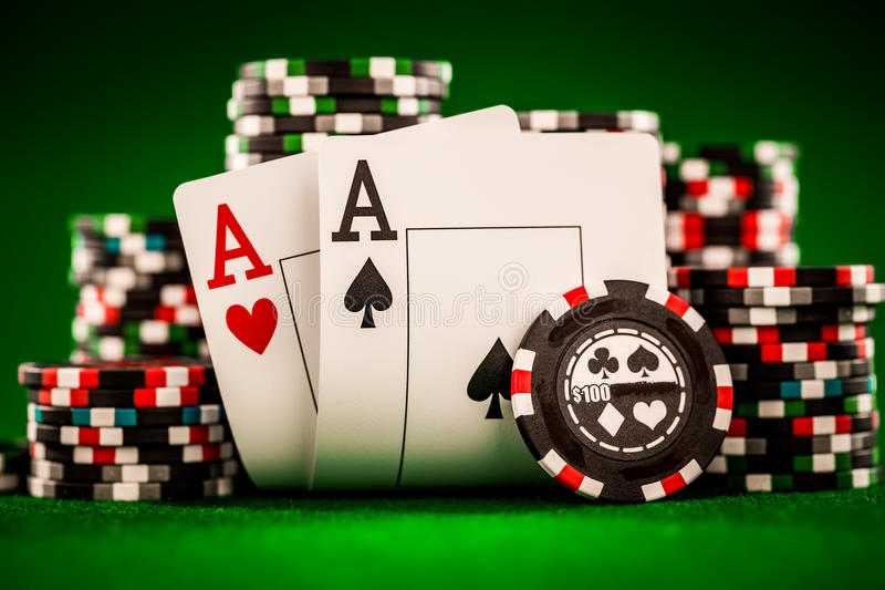 Chips and two aces. Stack of chips and two aces on the table on the green baize - poker game concept stock image