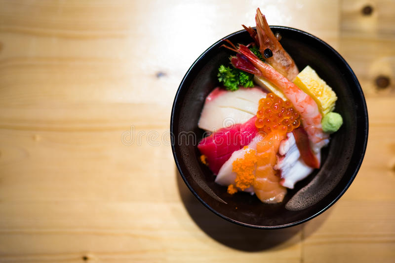 Chirashi sushi, Japanese food rice bowl with raw salmon sashimi, mixed seafood, top view, darken edge. Copy space on wooden table, focus on salmon eggs with royalty free stock photos