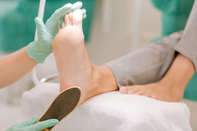 Chiropodist wearing gloves holding feet scrubber in her hand. Chiropodist in gloves. Professional experienced chiropodist wearing gloves holding feet scrubber in royalty free stock photo