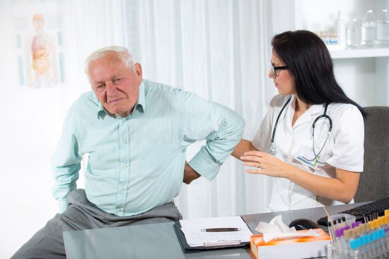 Chiropractic: Chiropractor που εξετάζει το ανώτερο άτομο στο γραφείο στοκ εικόνες