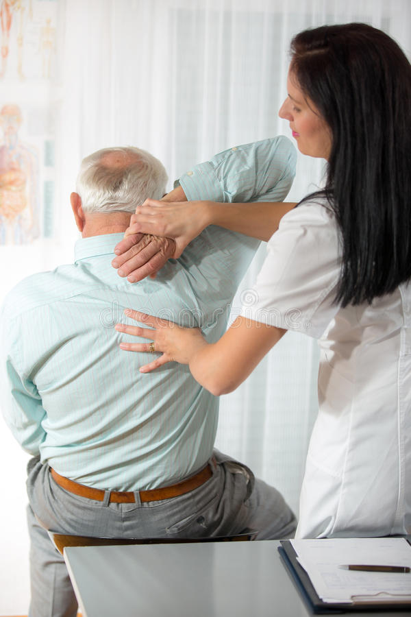 Chiropractic: Chiropractor που εξετάζει το ανώτερο άτομο στο γραφείο στοκ φωτογραφία