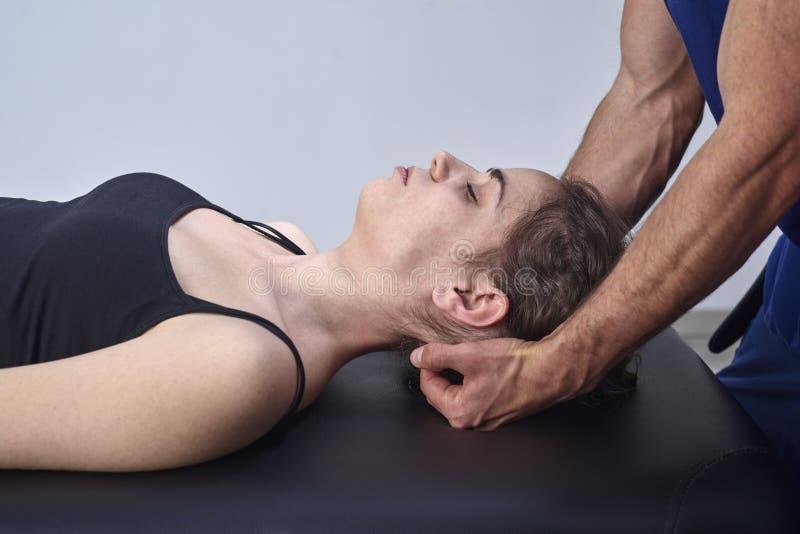Chiropractic som får mobilisering den cervikala ryggen av en kvinna Manuell terapi Neurological fysisk undersökning Osteopathy royaltyfria bilder
