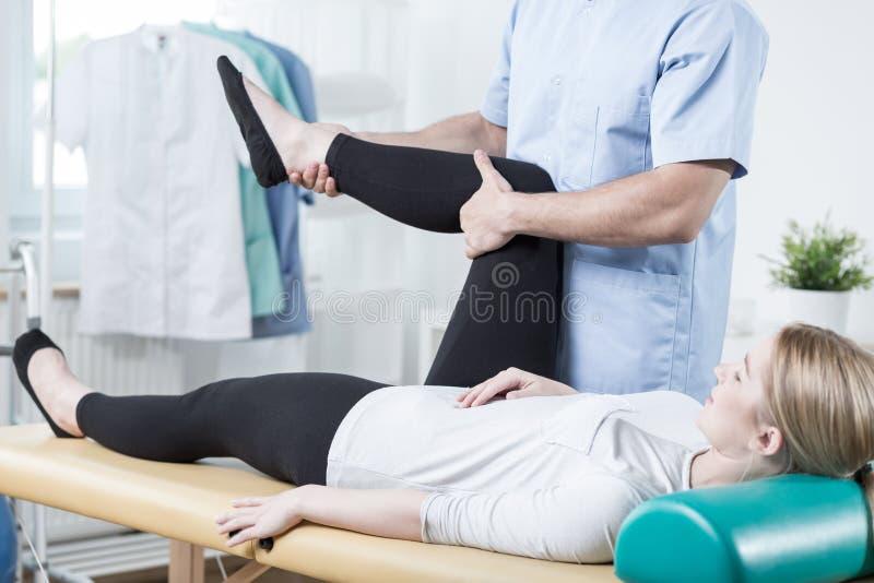 Chiropracticus die vrouwelijk been uitrekken stock afbeelding